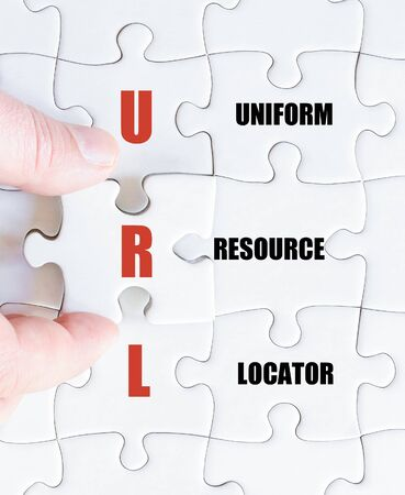 url: Hand of a business man completing the puzzle with the last missing piece.Concept image of Business Acronym URL as Uniform Resource Locator