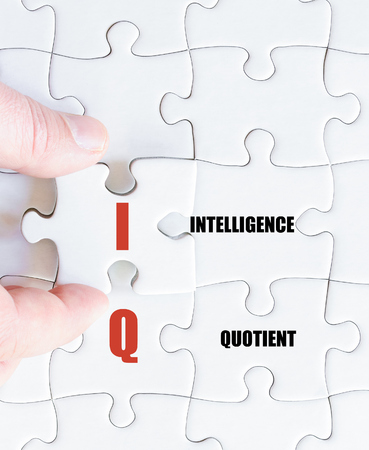 iq: Hand of a business man completing the puzzle with the last missing piece.Concept image of Business Acronym IQ as Intelligence Quotient