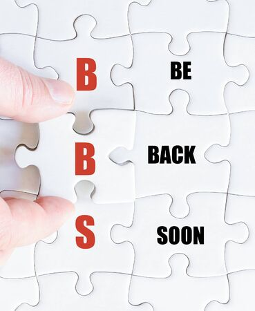 be missing: Hand of a business man completing the puzzle with the last missing piece.Concept image of Business Acronym BBS as Be Back Soon
