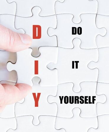 do it yourself: Hand of a business man completing the puzzle with the last missing piece.Concept image of Business Acronym DIY as Do It Yourself Stock Photo