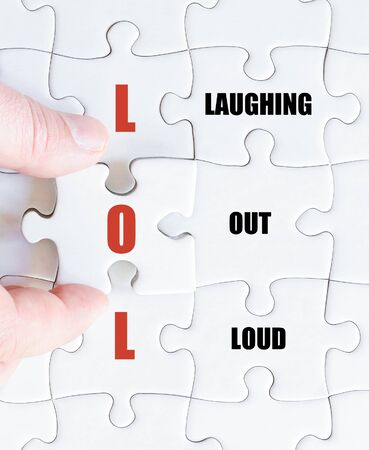 laughing out loud: Hand of a business man completing the puzzle with the last missing piece.Concept image of Social Media Acronym LOL as Laughing Out Loud Stock Photo
