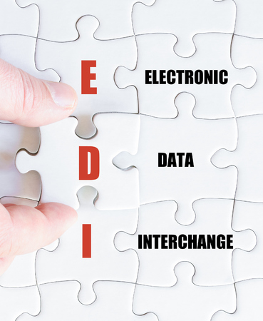 Hand of a business man completing the puzzle with the last missing piece.Concept image of Business Acronym EDI as Electronic Data Interchange