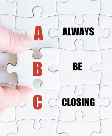 be missing: Hand of a business man completing the puzzle with the last missing piece.Concept image of Business Acronym ABC as Always Be Closing Stock Photo