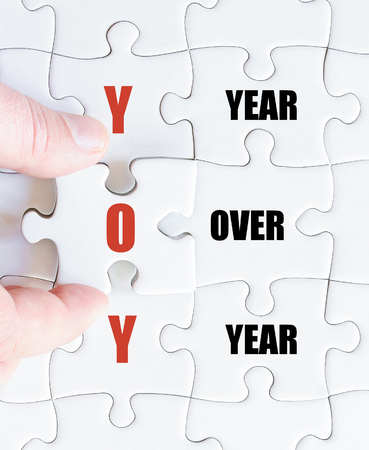yoy: Hand of a business man completing the puzzle with the last missing piece.Concept image of Business Acronym YOY as Year Over Year
