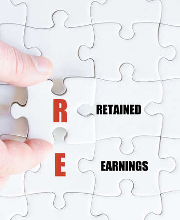 retained: Hand of a business man completing the puzzle with the last missing piece.Concept image of Business Acronym RE as Retained Earnings
