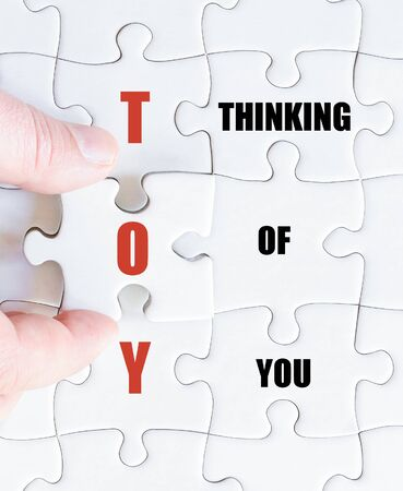 thinking of you: Hand of a business man completing the puzzle with the last missing piece.Concept image of Business Acronym TOY as Thinking Of You