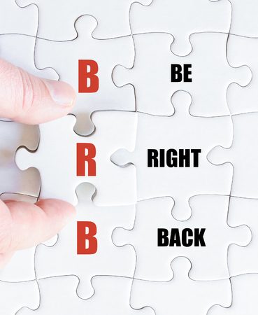 be missing: Hand of a business man completing the puzzle with the last missing piece.Concept image of Business Acronym BRB as Be Right Back