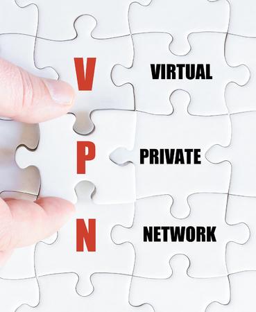 vpn: Hand of a business man completing the puzzle with the last missing piece.Concept image of Business Acronym VPN as Virtual Private Network