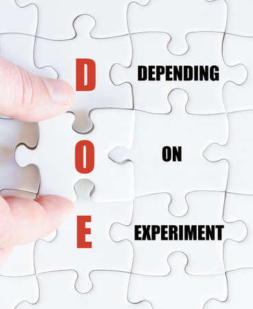 depending: Hand of a business man completing the puzzle with the last missing piece.Concept image of Business Acronym DOE as Depending On Experiment