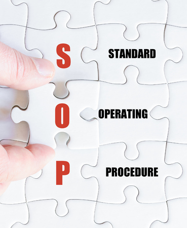 standards: Hand of a business man completing the puzzle with the last missing piece.Concept image of Business Acronym SOP as Standard Operating Procedure