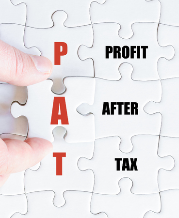 pat: Hand of a business man completing the puzzle with the last missing piece.Concept image of Business Acronym PAT as Profit After Tax