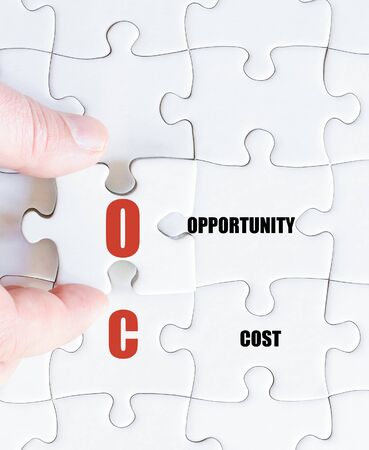 oc: Hand of a business man completing the puzzle with the last missing piece.Concept image of Business Acronym OC as Opportunity Cost Stock Photo