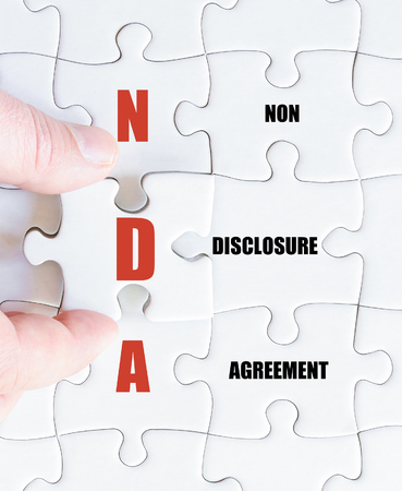 disclosure: Hand of a business man completing the puzzle with the last missing piece.Concept image of Business Acronym NDA as Non Disclosure Agreement Stock Photo