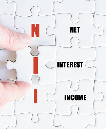 net income: Hand of a business man completing the puzzle with the last missing piece.Concept image of Business Acronym NII as Net Interest Income