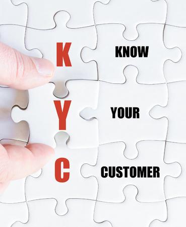 Hand van een zakenman die de puzzel voltooit met het laatste ontbrekende stuk. Conceptimago van bedrijf Acroniem KYC as Know Your Customer Stockfoto