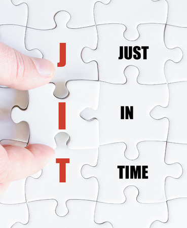 just in time: Hand of a business man completing the puzzle with the last missing piece.Concept image of Business Acronym JIT as Just In Time