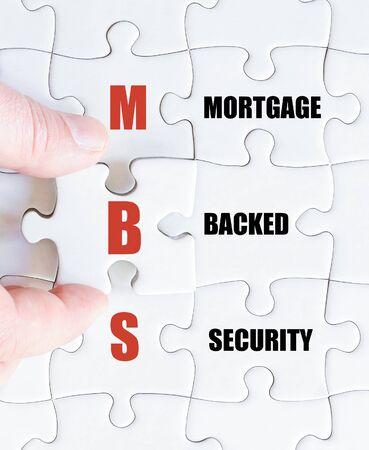 最後の行方不明の部分とパズルを完了するビジネスの男の手。住宅ローン担保証券としてビジネスの頭字語 MBS のコンセプト イメージ 写真素材
