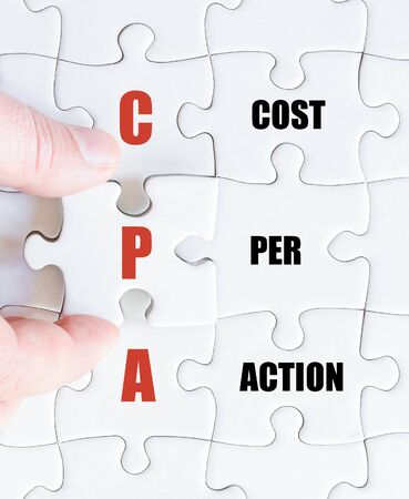 cpa: Hand of a business man completing the puzzle with the last missing piece.Concept image of Business Acronym CPA as Cost Per Action