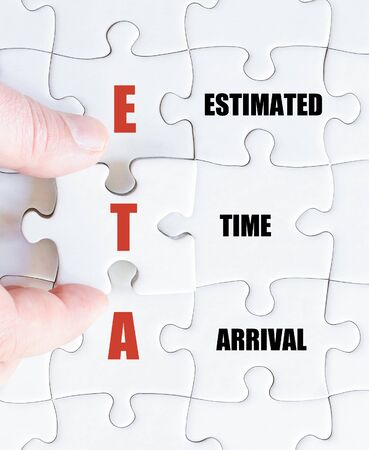 estimated: Hand of a business man completing the puzzle with the last missing piece.Concept image of Business Acronym ETA as Estimated Time Arrival