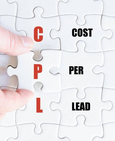 cpl: Hand of a business man completing the puzzle with the last missing piece.Concept image of Business Acronym CPL as Cost Per Lead Stock Photo