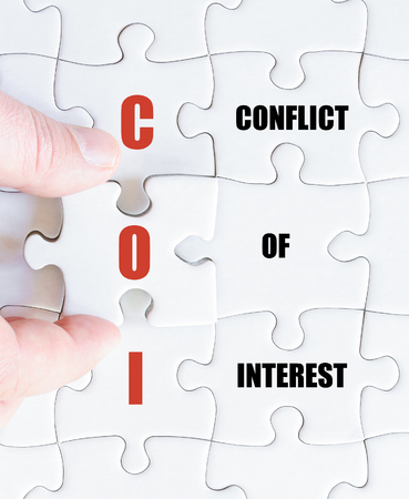 coi: Hand of a business man completing the puzzle with the last missing piece.Concept image of Business Acronym COI as Conflict Of Interest