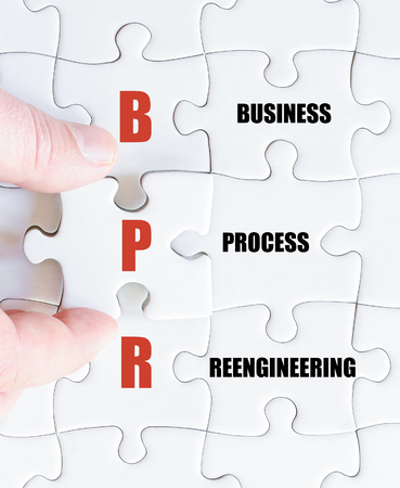reengineering: Hand of a business man completing the puzzle with the last missing piece.Concept image of Business Acronym BPR as Business Process Reengineering