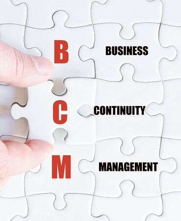 continuity: Hand of a business man completing the puzzle with the last missing piece.Concept image of Business Acronym BCM as Business Continuity Management Stock Photo