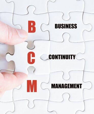 最後の行方不明の部分とパズルを完了するビジネスの男の手。ビジネス略語 BCM 事業継続マネジメントとしてのコンセプト イメージ