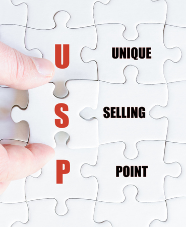 selling points: Hand of a business man completing the puzzle with the last missing piece.Concept image of Business Acronym USP as Unique Selling Point