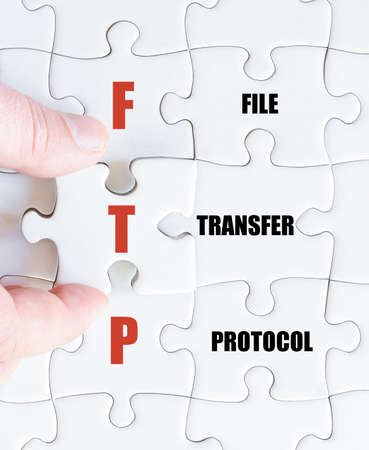 ftp: Hand of a business man completing the puzzle with the last missing piece.Concept image of Business Acronym FTP as File Transfer Protocol