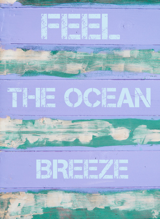 by feel: Concept image of FEEL THE OCEAN BREEZE  motivational quote written on vintage painted wooden wall Stock Photo