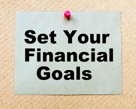 financial goals: Set Your Financial Goals written on paper note pinned with red thumbtack on wooden board. Business conceptual Image