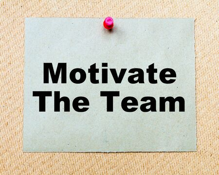 Motivate The Team written on paper note pinned with red thumbtack on wooden board. Business conceptual Image