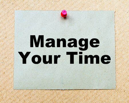 thumbtack: Manage Your Time written on paper note pinned with red thumbtack on wooden board. Business conceptual Image