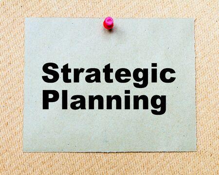 planificacion estrategica: Planificación Estratégica escrito en la nota de papel clavado con chincheta roja sobre tabla de madera. Negocios imagen conceptual