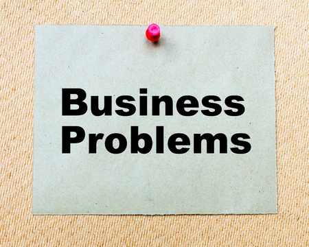 business problems: Business Problems  written on paper note pinned with red thumbtack on wooden board. Business conceptual Image