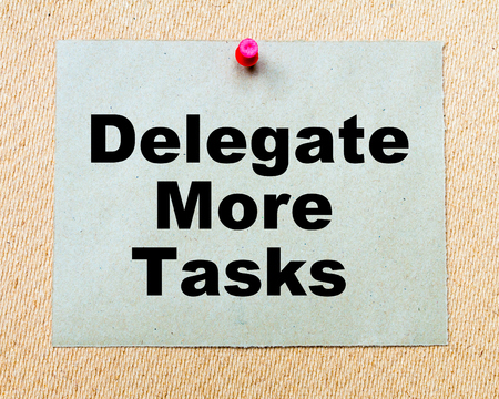 delegar: Delegar M�s tareas escritas en la nota de papel clavado con chincheta roja sobre tabla de madera. Negocios imagen conceptual Foto de archivo