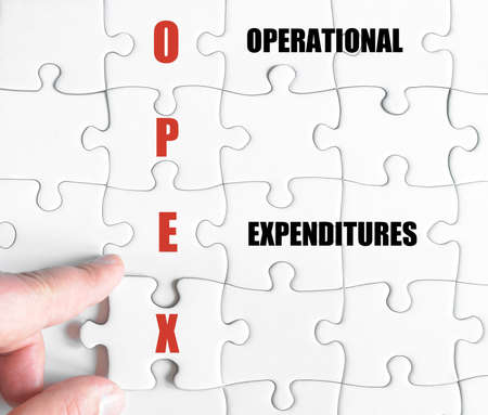 operational: Hand of a business man completing the puzzle with the last missing piece.Concept image of Business Acronym OPEX as Operational Expenditures Stock Photo