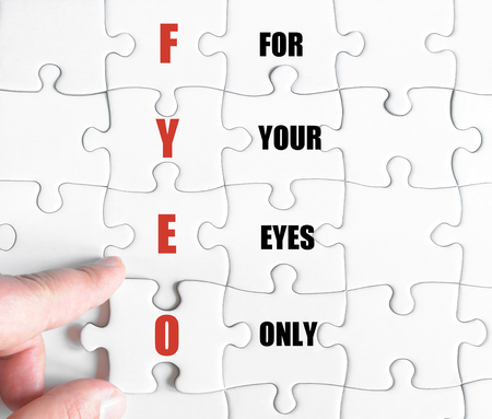 close your eyes: Hand of a business man completing the puzzle with the last missing piece.Concept image of Business Acronym FYEO as For Your Eyes Only Stock Photo