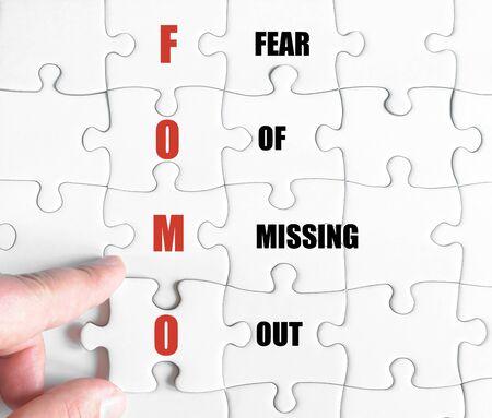 最後の行方不明の部分とパズルを完了するビジネスの男の手。ビジネス略語 FOMO 恐怖の行方不明であるとのコンセプト イメージ 写真素材