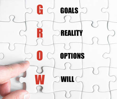 Hand of a business man completing the puzzle with the last missing piece.Concept image of Business Acronym GROW as Goals Reality Options Will