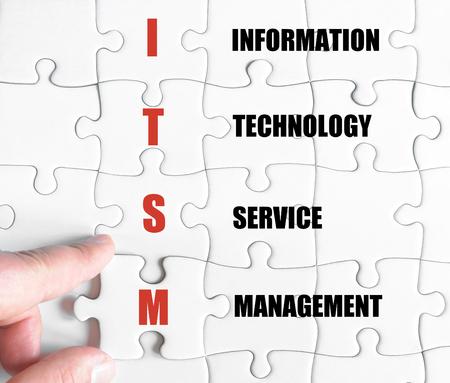 最後の行方不明の部分とパズルを完了するビジネスの男の手。情報技術サービス管理とビジネス頭字語 ITSM のコンセプト イメージ 写真素材