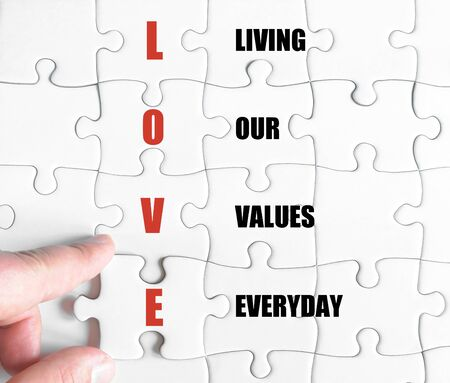 our: Hand of a business man completing the puzzle with the last missing piece.Concept image of Business Acronym LOVE as Living Our Values Everyday