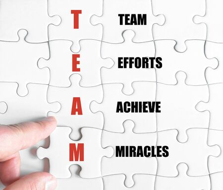 efforts: Hand of a business man completing the puzzle with the last missing piece.Concept image of Business Acronym TEAM as Team Efforts Achieve Miracles