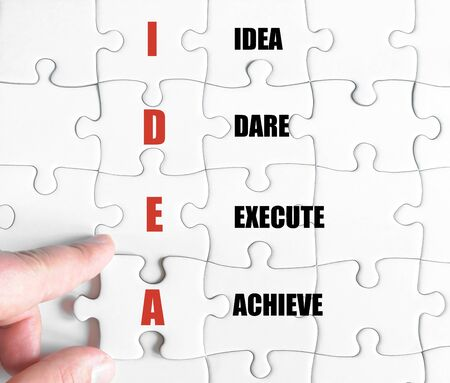 dare: Hand of a business man completing the puzzle with the last missing piece.Concept image of Business Acronym IDEA as Idea Dare Execute Achieve