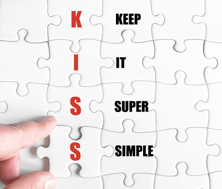 super man: Hand of a business man completing the puzzle with the last missing piece.Concept image of Business Acronym KISS as Keep It Super Simple Stock Photo