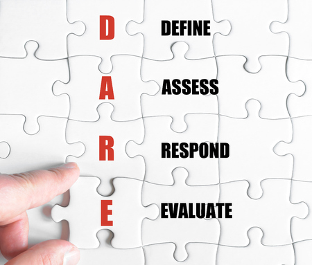 define: Hand of a business man completing the puzzle with the last missing piece.Concept image of Business Acronym DARE as Define Assess Respond Evaluate Stock Photo