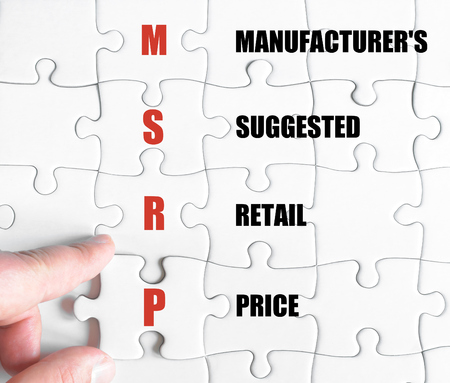 suggested: Hand of a business man completing the puzzle with the last missing piece.Concept image of Business Acronym MSRP as Manufacturers Suggested Retail Price