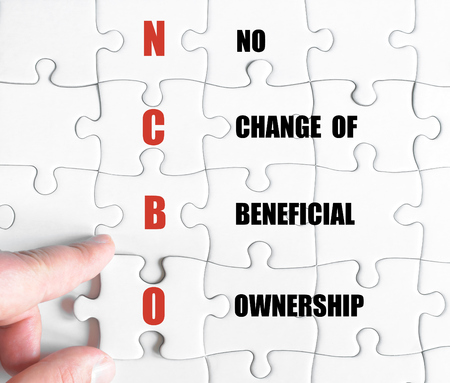 beneficial: Hand of a business man completing the puzzle with the last missing piece.Concept image of Business Acronym NCBO as No Change Of Beneficial Ownership