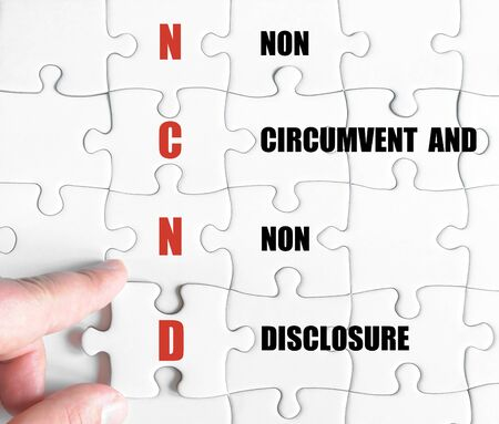 circumvent: Hand of a business man completing the puzzle with the last missing piece.Concept image of Business Acronym NCND as Non Circumvent And Non Disclosure
